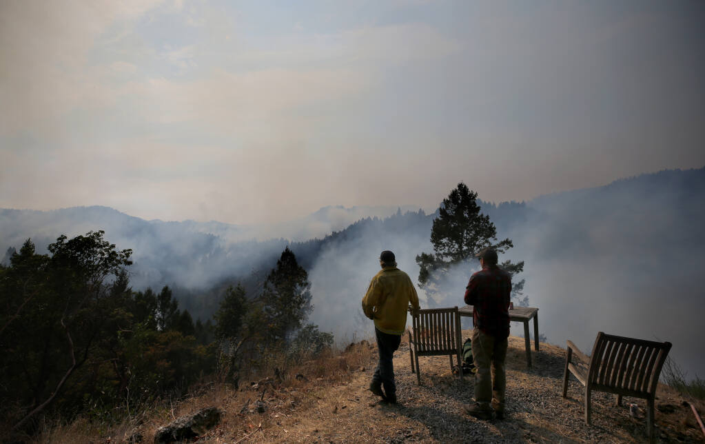 Members of the Peterson family look out from their Sweetwater Springs Road property towards Armstrong Redwoods State Natural Reserve as smoke from the Walbridge fire rises above the trees in Guerneville, Calif., on Sunday, Aug. 23, 2020. (BETH SCHLANKER/ The Press Democrat)