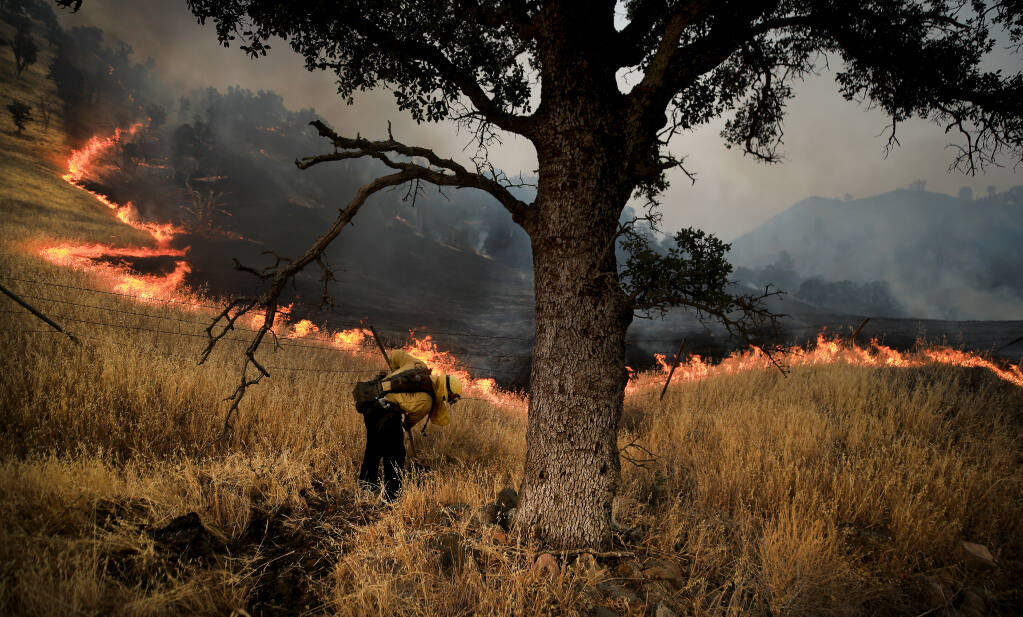 Along Highway 16 in Yolo County, fire crews monitor the eastern edge of the Hennessey fire as it backs down a mountain in the Rumsey Canyon, Friday, August 28, 2020.  (Kent Porter / The Press Democrat) 2020