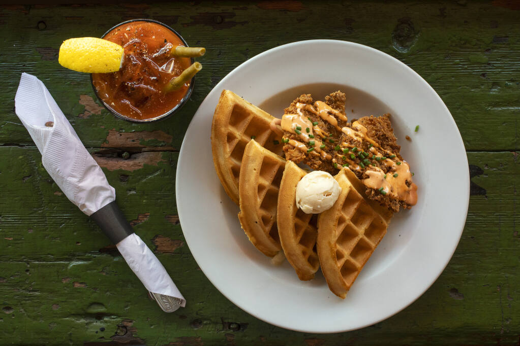 Chicken & Waffles comes with sriracha cream and organic maple butter, served here with a Bloody Mary, at Gypsy Cafe in Sebastopol. (John Burgess / The Press Democrat)