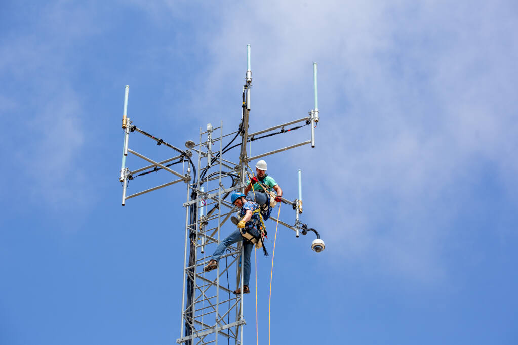 Dustin Mair, top, and Vince Hurst prepare to install a new camera on the top of the 80-foot tower at the Sheriff's Office telecommunications facility at Sonoma Raceway on Thursday, July 15, 2021. (Photo by Robbi Pengelly/Index-Tribune)