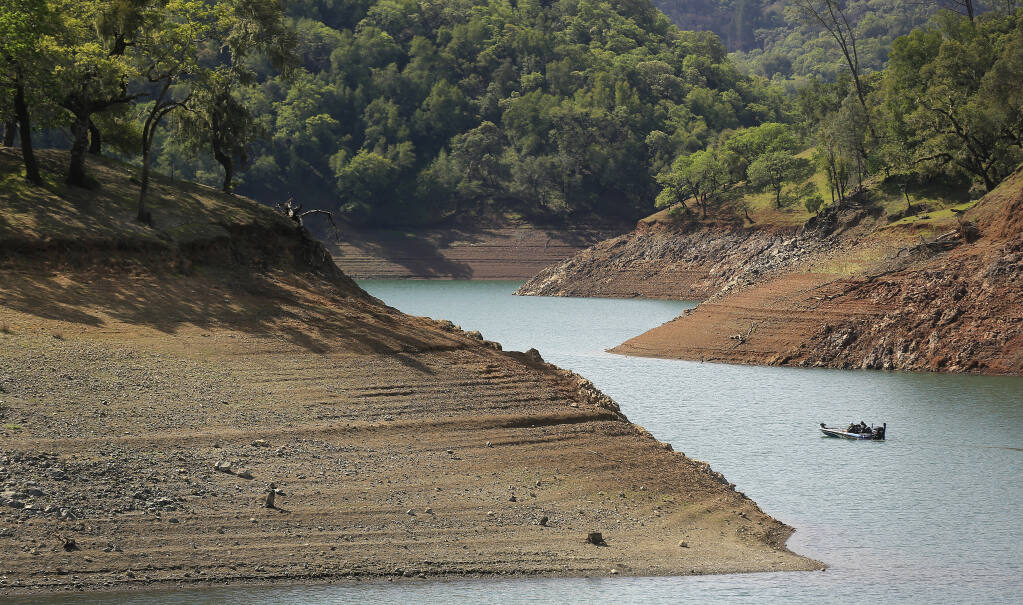 A boater navigates Lake Sonoma and its ever increasing steep shoreline, Friday, April 2, 2021,  200 yards west of the private marina. The lake is at 63.09% of capacity, the lowest point in history for this time of year.  (Kent Porter / The Press Democrat)