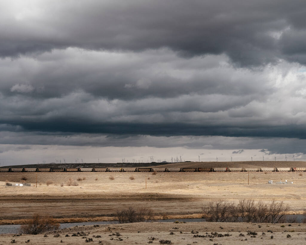 A train of coal cars crosses the desert plain as wind turbines operate in the distance on land reclaimed after strip-mining, near Glenrock, Wyo., Feb. 3, 2021. (Benjamin Rasmussen/The New York Times)