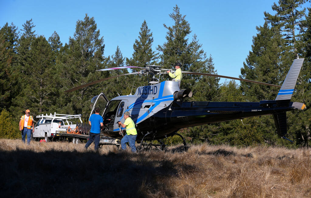 A Heli-Dunn crew refuels one of the company's Heli-Saws at a landing zone near Tin Barn Road in northwest Sonoma County before returning to trim trees along PG&E transmission lines on Tuesday, Dec. 8, 2020. (Christopher Chung / The Press Democrat)