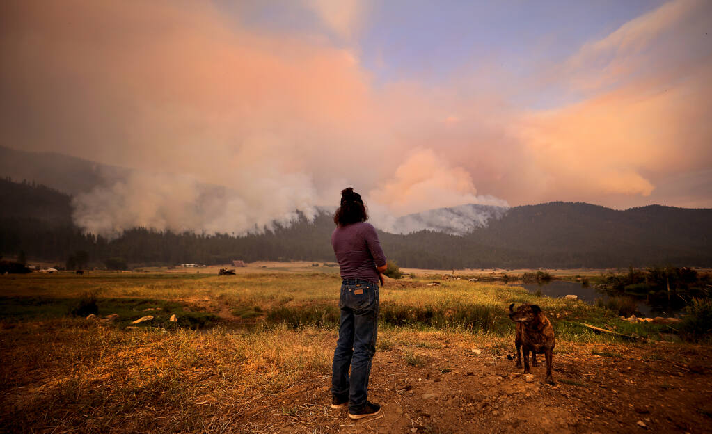 Marsha Melton of Greenville watches as the Dixie fire burns into Indian Valley, Sunday, July 8, 2021. Greenville, with a population of about 1,200, was obliterated by the nearly 500,000-acre fire.  (Kent Porter / The Press Democrat)