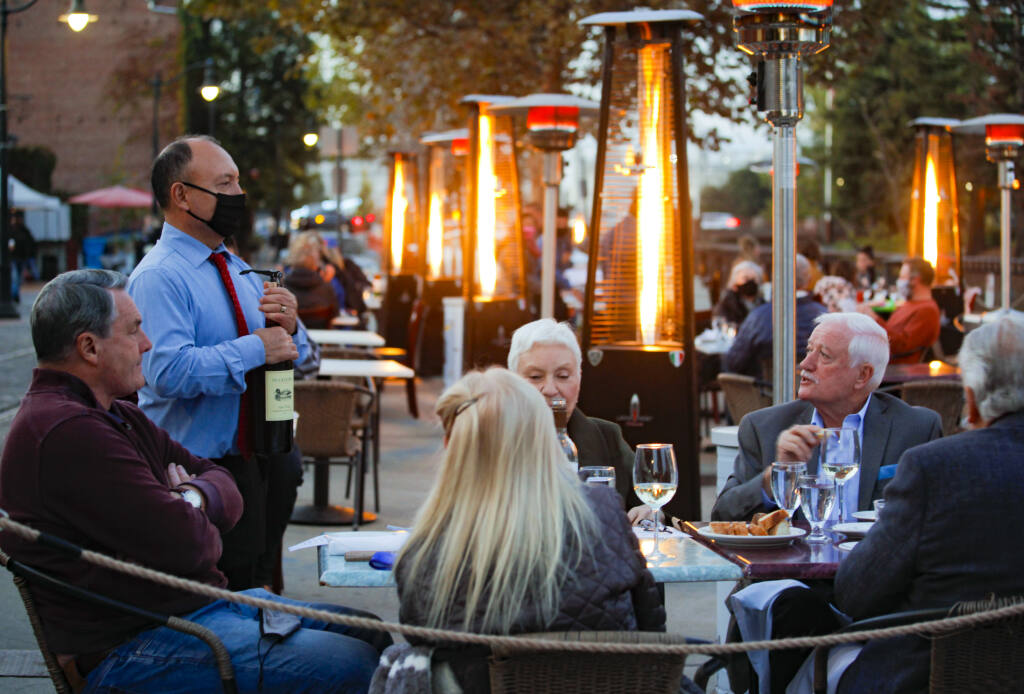 Juan Gopar, a server at Cucina Paradiso opens a bottle of wine for guests.  The downtown Petaluma restaurant serves dinner at the outdoor tables placed on Water Street.(CRISSY PASCUAL/ARGUS-COURIER STAFF)
