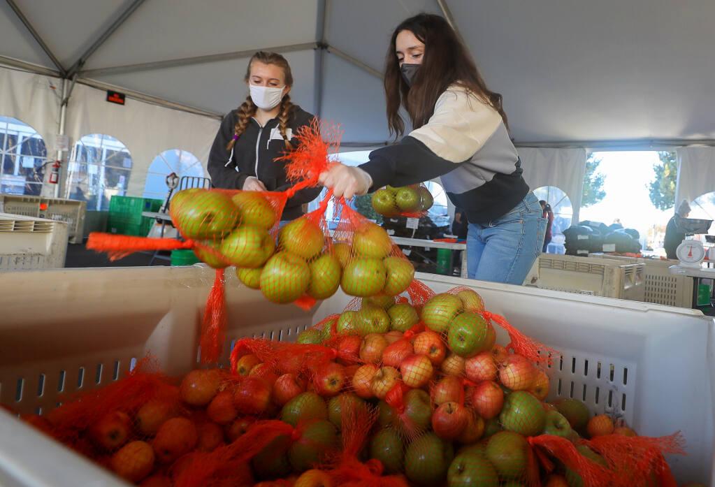Alex Barnes, right, and Capri Reed pack bags of apples at Redwood Empire Food Bank, north of Santa Rosa on Monday, Nov. 23, 2020. (Christopher Chung / The Press Democrat)