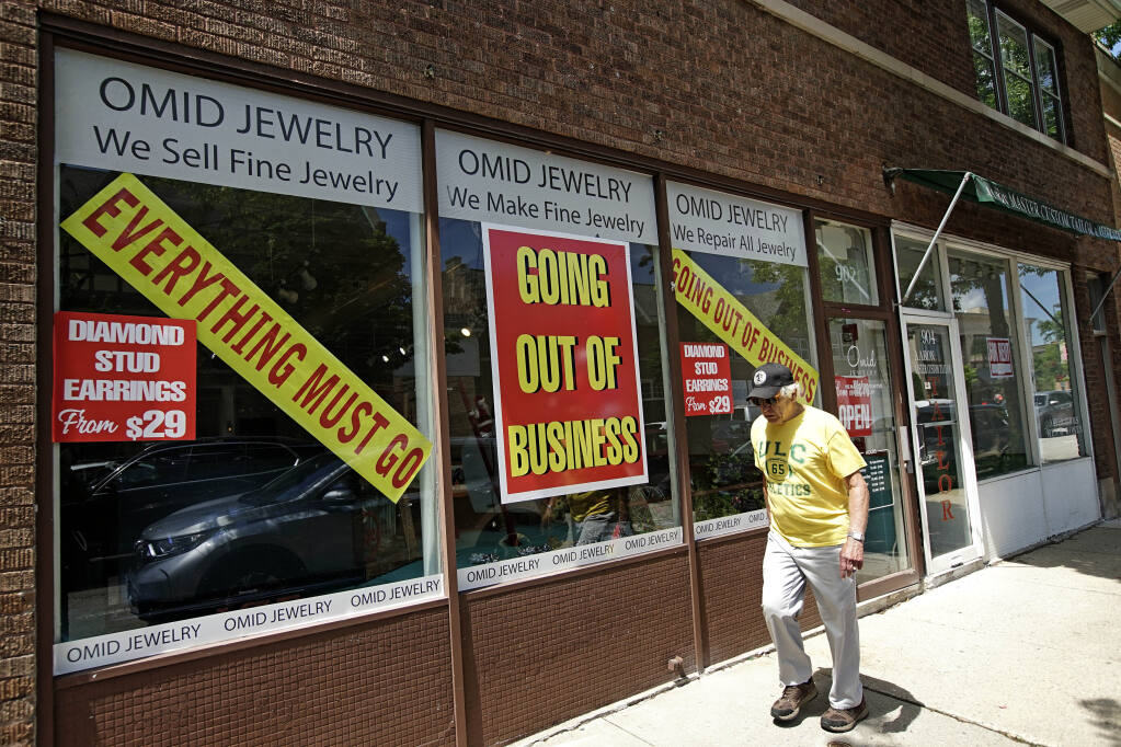 A man walks past a retail store that is going out of business due to the coronavirus pandemic in Winnetka, Ill., Tuesday, June 23, 2020. Illinois Gov. J.B Pritzker announced a package of state grant programs that will help support communities and businesses impacted by the COVID-19 pandemic and unrest in the area. (AP Photo/Nam Y. Huh)