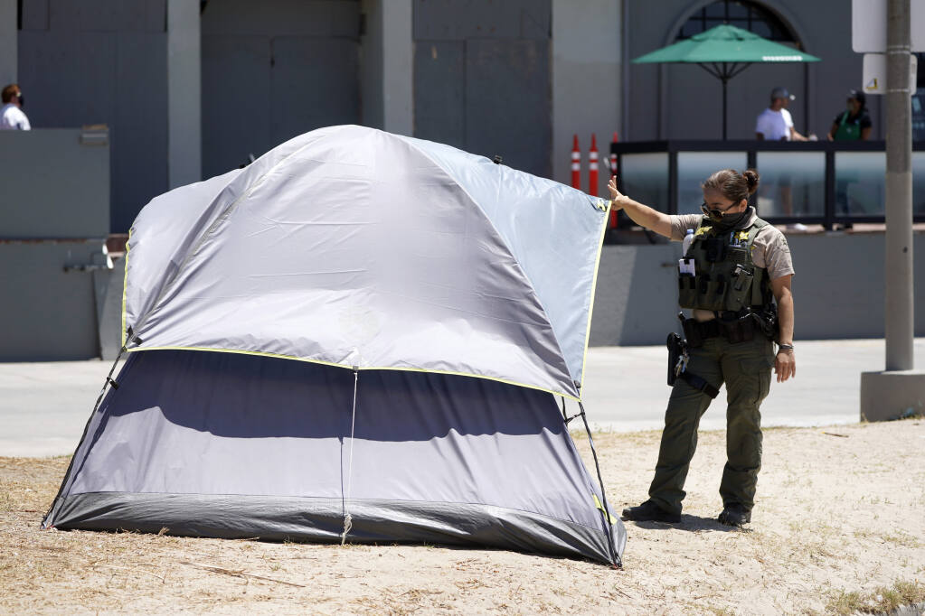 A member of Los Angeles County Sheriffs Department's HOST, Homeless Outreach Service Team, talks to a homeless person Tuesday, June 8, 2021, in the Venice Beach section of Los Angeles. (AP Photo/Marcio Jose Sanchez)