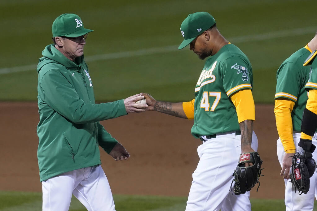 Oakland Athletics pitcher Frankie Montas hands the ball to manager Bob Melvin as he is taken out for a relief pitcher during the seventh inning against the Kansas City Royals in Oakland on Thursday, June 10, 2021. (Jeff Chiu / ASSOCIATED PRESS)