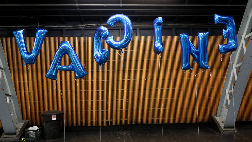 """Balloons spelling out """"vaccine"""" decorate the Sonoma County Medical Association coronavirus vaccination site, at the Sonoma County Fairgrounds, in Santa Rosa on Wednesday, Feb.  3, 2021.  (Christopher Chung / The Press Democrat)"""
