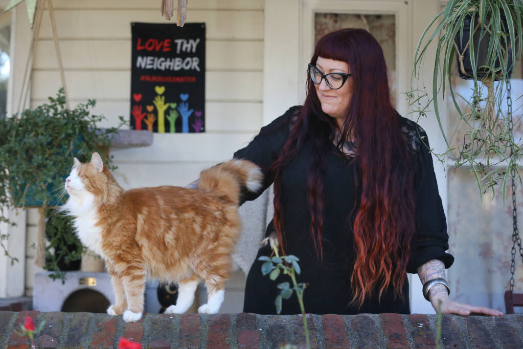 Anna Hill pets her cat, Murdock, outside her home in Santa Rosa on Monday, Dec. 14, 2020. (Beth Schlanker / The Press Democrat)