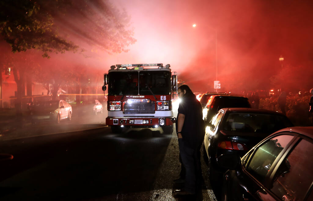 Residents of an apartment complex on Burt Street in Santa Rosa are evacuated as Santa Rosa firefighters work to contain an apartment fire in Santa Rosa, Saturday, May 22, 2021 that went to two alarms. The fire displaced several families who sought help from the Red Cross.  (Kent Porter / Santa Rosa Press Democrat)