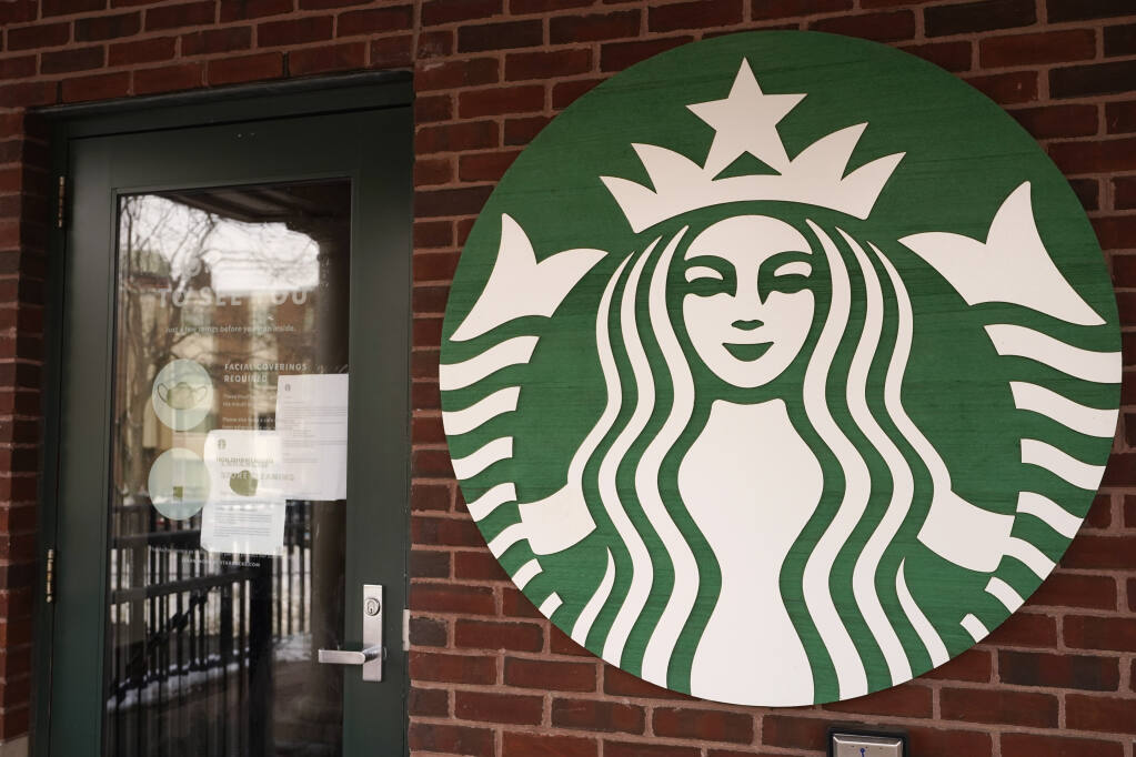 A Starbucks coffee company logo and information signs are seen at Palatine Metra train station in Palatine, Ill., Wednesday, Jan. 6, 2021. (AP Photo/Nam Y. Huh)