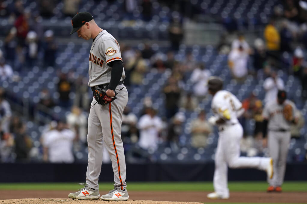 San Francisco Giants starting pitcher Anthony DeSclafani, left, stands on the mound as the San Diego Padres' Manny Machado rounds the bases after hitting a three-run home run during the first inning on Saturday, May 1, 2021, in San Diego. (Gregory Bull / ASSOCIATED PRESS)