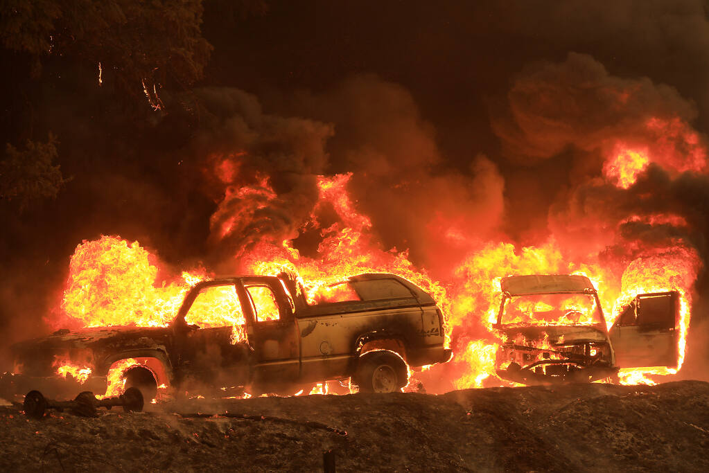 A home, background, and cars catch fire along Highway 101 north of Willits, Monday, Sept. 7, 2020 as the Oak fire burns nearly 1,000 acres. (Kent Porter / The Press Democrat) 2020