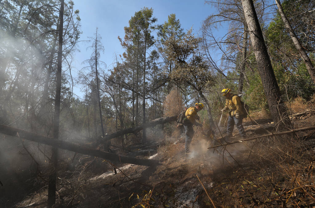 Los Angeles City Fire Department firefighters work on extinguishing hot spots along Pony Gate Trail in Sugarloaf Ridge State Park on Monday, Oct. 5, 2020.  (Christopher Chung / The Press Democrat)