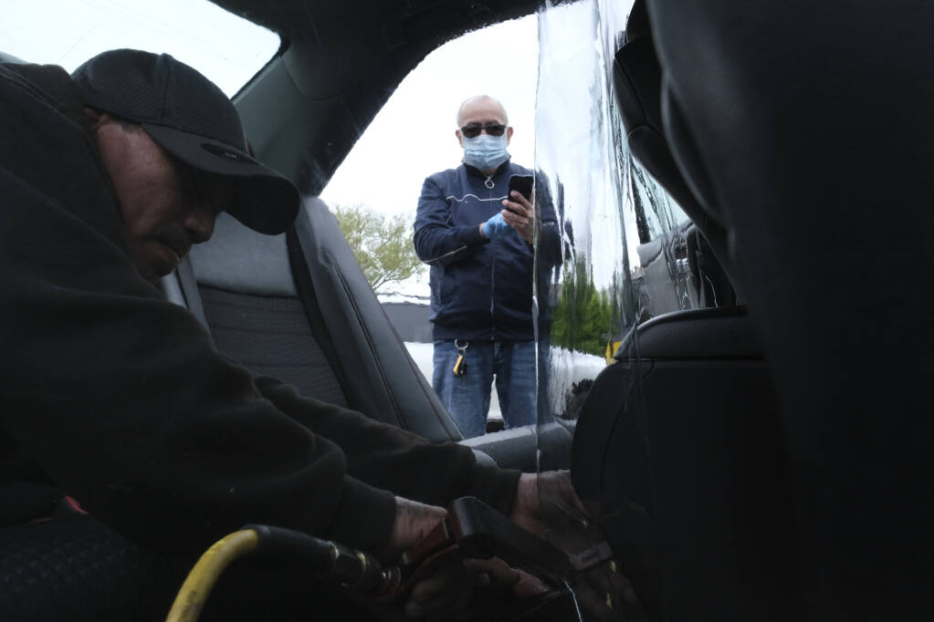 FILE - In this  May 6, 2020, file photo, Luis Hidalgo, wearing face mask, watches as Joel Rios installs a plastic barrier in his car to protect himself and his passengers from the new coronavirus in the Bronx borough of New York. Mask slackers will now have to provide photographic proof they're wearing a face covering before boarding an Uber. The San Francisco-based company unveiled a new policy Tuesday, Sept. 1, stipulating that if a driver reports to Uber that a rider wasn't wearing a mask, the rider will have to take a selfie with one strapped on the next time they summon a driver on the world's largest ride-hailing service. (AP Photo/Seth Wenig, File)