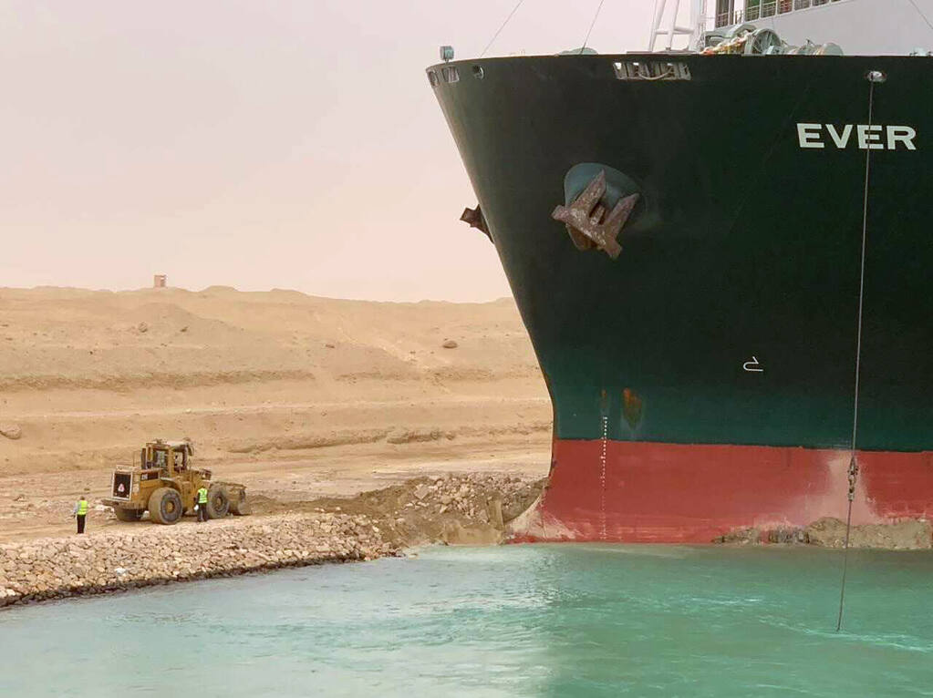 A cargo ship, named the Ever Given, sits with its bow stuck into the wall Wednesday, March 24, 2021, after it become wedged across Egypt's Suez Canal and blocked all traffic in the vital waterway. (Suez Canal Authority)