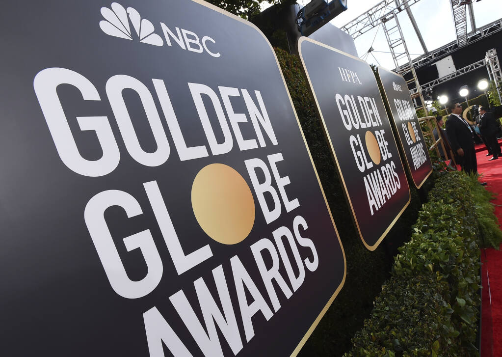 """FILE - Event signage appears above the red carpet at the 77th annual Golden Globe Awards, Sunday, Jan. 5, 2020, in Beverly Hills, Calif. More than 100 Hollywood publicity firms that collectively represent the majority of stars in film and television, said they will advise their clients to skip the Golden Globes if the Hollywood Foreign Press Association does not commit to """"transformational change.""""  (Photo by Jordan Strauss/Invision/AP, File)"""