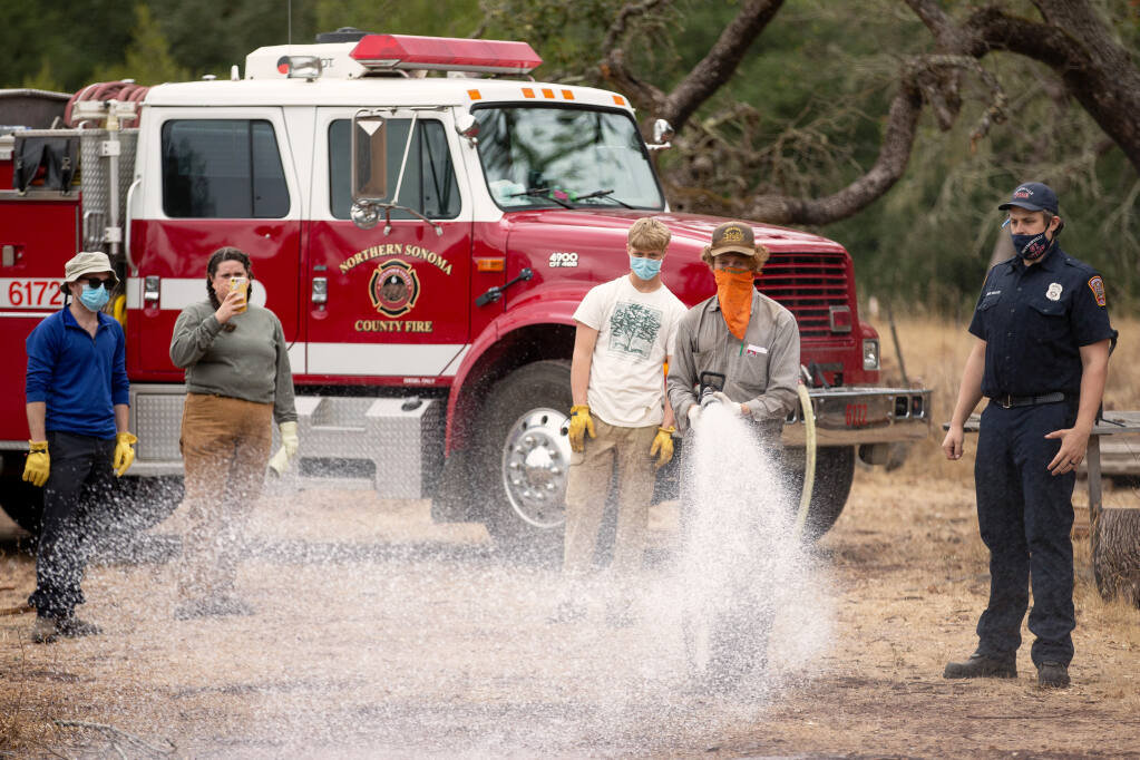 Volunteer Jake Olson sprays water from a fire engine bumper line as instructed by Northern Sonoma County Fire Protection District firefighter Andrew Wallace, at right, during basic wildland firefighting skills training by Audubon Canyon Ranch's Fire Forward program at Bouverie Preserve near Glen Ellen on Saturday, Oct. 10, 2020. (Alvin A.H. Jornada / The Press Democrat)