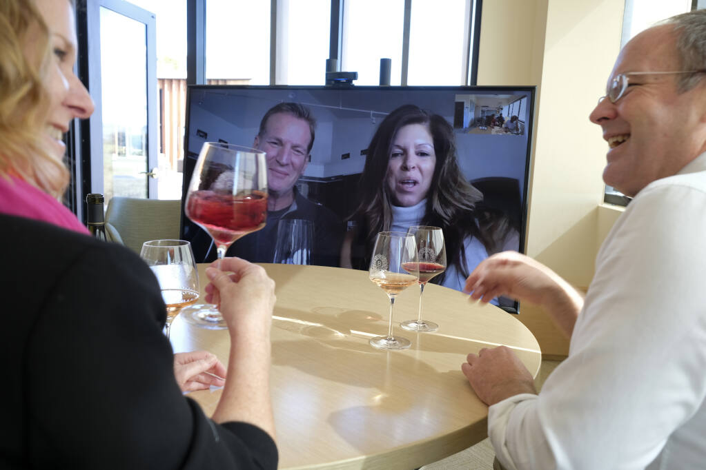Don Overly and his wife Mardel take part in a live virtual wine tasting from their home near Reno, Nev., with Bouchaine Vineyards winemaker and general manager Chris Kajani, left, and sales director Brian Allard Thursday, March 19, 2020, in Napa. While a number of North Coast wineries have reopened for outdoor tasting, virtual sessions are an enduring legacy of the coronavirus pandemic. (AP Photo/Eric Risberg)