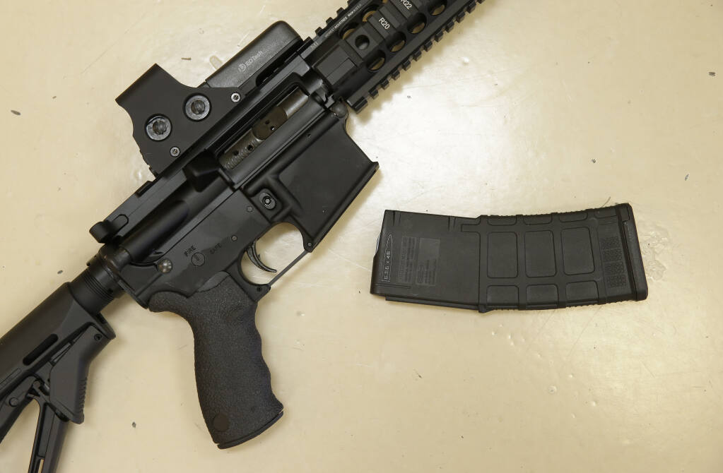 """FILE - In this Oct. 3, 2013, file photo, a custom-made semi-automatic hunting rifle with a high-capacity detachable magazine is displayed at TDS Guns in Rocklin, Calif. U.S. District Judge Roger Benitez of San Diego ruled Friday, June 4, 2021, that the state's definition of illegal military-style rifles unlawfully deprives law-abiding Californians of weapons commonly allowed in most other states and by the U.S. Supreme Court. California Gov. Gavin Newsom condemned the decision, calling it """"a direct threat to public safety and the lives of innocent Californians, period."""" (AP Photo/Rich Pedroncelli, File)"""