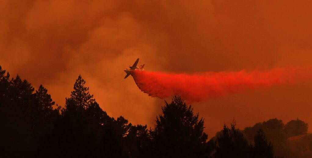A Cal Fire pilot maneuver's an S2-T tanker to make a drop on the Walbridge fire at sunset near Healdsburg, Wednesday, August 19, 2020. (Kent Porter / The Press Democrat) 2020