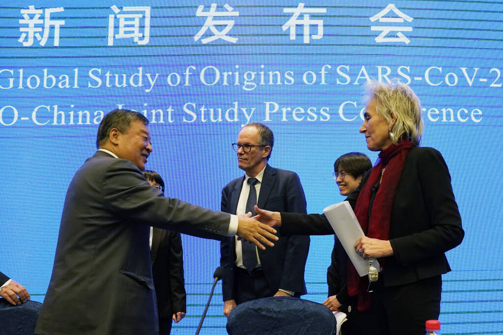 """Marion Koopmans, right, and Peter Ben Embarek, center, of the World Health Organization team say farewell to their Chinese counterpart Liang Wannian, left, after a WHO-China Joint Study Press Conference held at the end of the WHO mission in Wuhan, China, on Feb. 9. A joint WHO-China study on the origins of COVID-19 says that transmission of the virus from bats to humans through another animal is the most likely scenario and that a lab leak is """"extremely unlikely."""" (Ng Han Guan / Associated Press)"""
