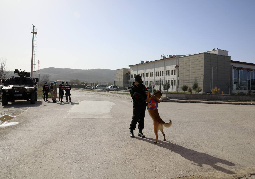 Bulent Okurcan, a military police officer stands with his 7-year-old Belgian wolf, Ihbar, as people wait outside a courthouse before the trial of 497 defendants, in Sincan, outside the capital Ankara, Turkey, Wednesday, April 7, 2021. The court was expected to deliver a verdict in their trial for involvement in a failed coup attempt in 2026. The court was expected to deliver a verdict in their trial for involvement in a failed coup attempt in 2026.(AP Photo/Burhan Ozbilici)