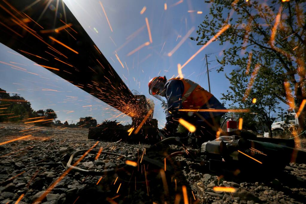 Isiah Romero, an employee of Holland LP, grinds a piece of rail after it was welded as part of a 3-mile extension of the SMART line in Windsor on Tuesday, July 14, 2020. (Beth Schlanker / The Press Democrat)