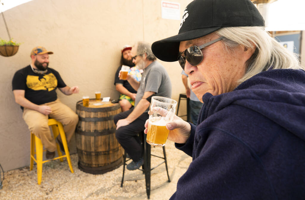 John Dang has a beer with friends at the Cooperage Brewing Co. in Santa Rosa on Friday, March 12, 2021. New state laws will allow breweries to serve beer without food beginning Saturday. (John Burgess / The Press Democrat)