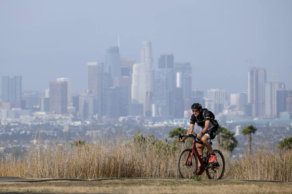 Steven Thorpe, 62, of Manhattan Beach, rides in the heat on Kenneth Hahn State Recreation Area Wednesday, June 16, 2021, in Los Angeles. (AP Photo/Ringo H.W. Chiu)