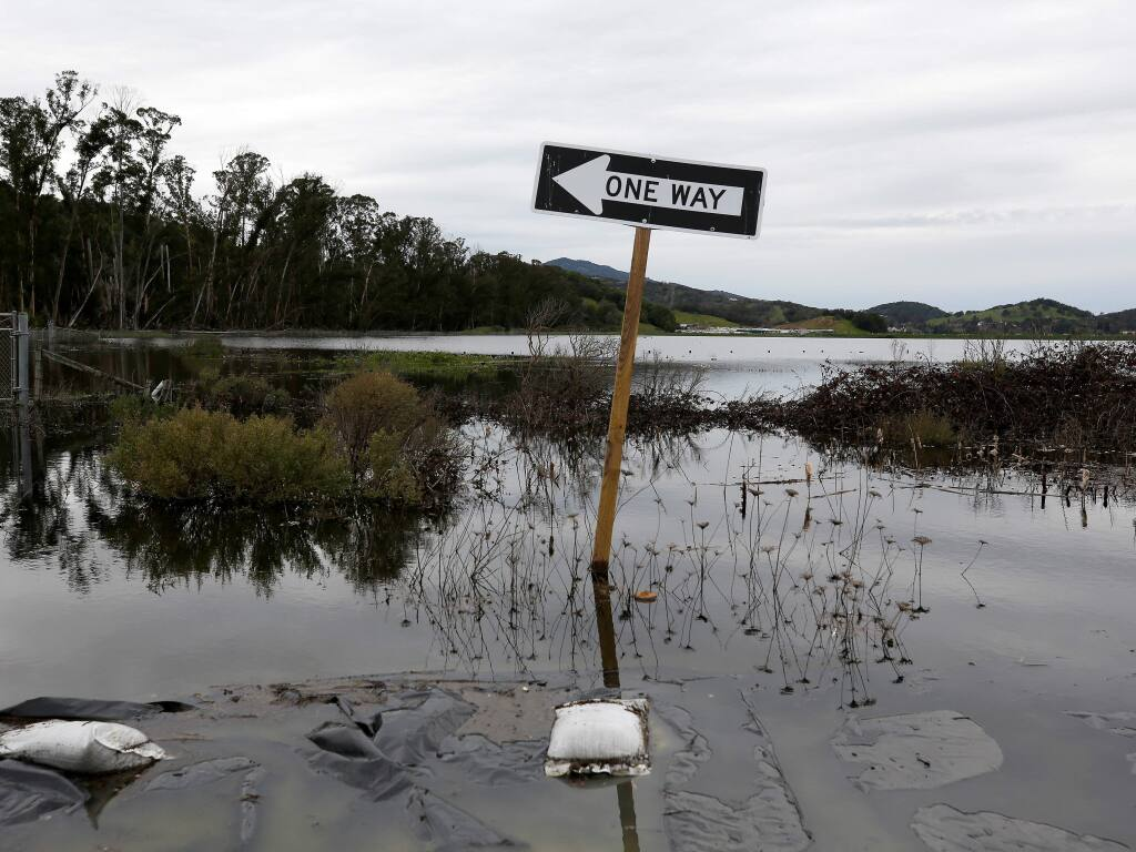 A partially submerged road sign alongside a flooded Highway 37. A state legislative analyst's report warns that rising seas levels could inundate the highway. (ALVIN JORNADA / The Press Democrat, 2019)