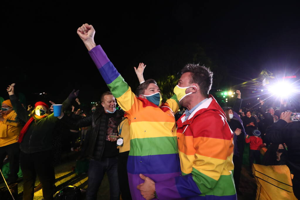 People celebrate in Brisbane, Australia, Wednesday, July 21, 2021, following an announcement by the International Olympic Committee that Brisbane was picked to host the 2032 Olympics. The Australian city was the inevitable winner of a one-candidate race steered by the IOC to avoid rival bids. (Jason O'Brien/AAP Image via AP)