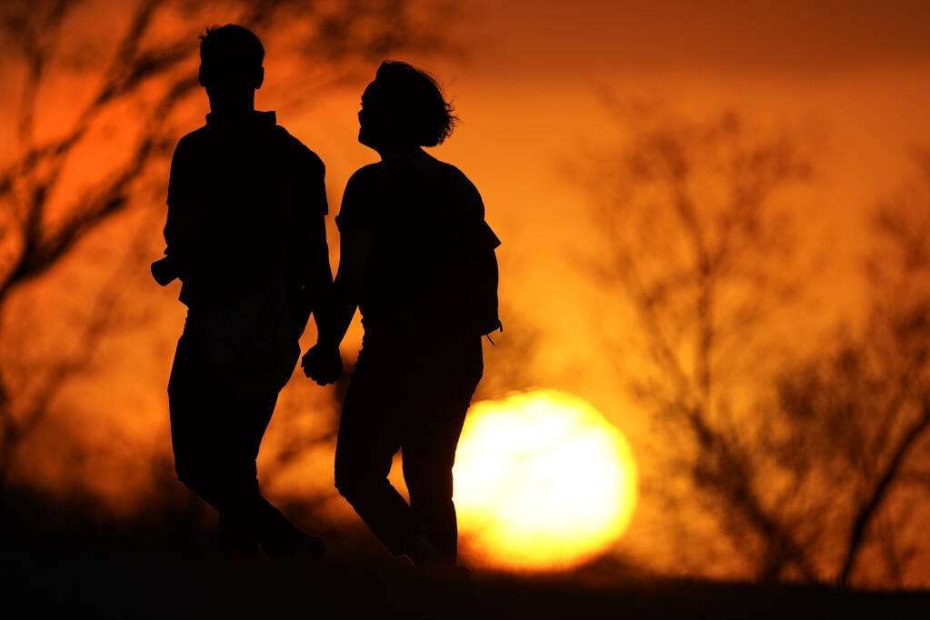 FILE - In this Wednesday, March 10, 2021 file photo, a couple walks through a park at sunset in Kansas City, Mo. According to a report released by the Centers for Disease Control and Prevention on Tuesday, July 20, 2021, U.S. life expectancy fell by a year and a half in 2020, the largest one-year decline since World War II. Worse, the decrease for both Black Americans and Hispanic Americans was a staggering three years. The decrease is due mainly to the COVID-19 pandemic, which health officials say is responsible for close to 74% of the overall life expectancy decline.  (AP Photo/Charlie Riedel, File)