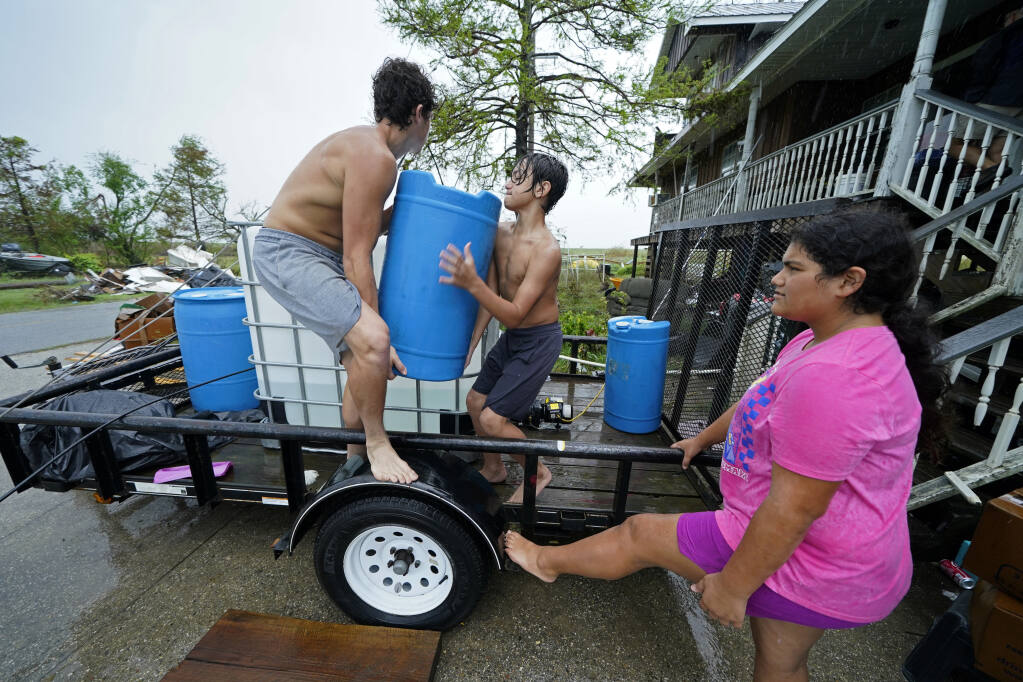 Terren Dardar, 17, left, Dayton Verdin, 14, and Lerryn Brune, 10, move barrels of rainwater they collected from Tropical Storm Nicholas, in the aftermath of Hurricane Ida in Pointe-aux-Chenes, La., Tuesday, Sept. 14, 2021. They have had no running water since the hurricane, and collected 140 gallons of rainwater in two hours from the tropical storm, which they filter and pump into their house for showers. (AP Photo/Gerald Herbert)