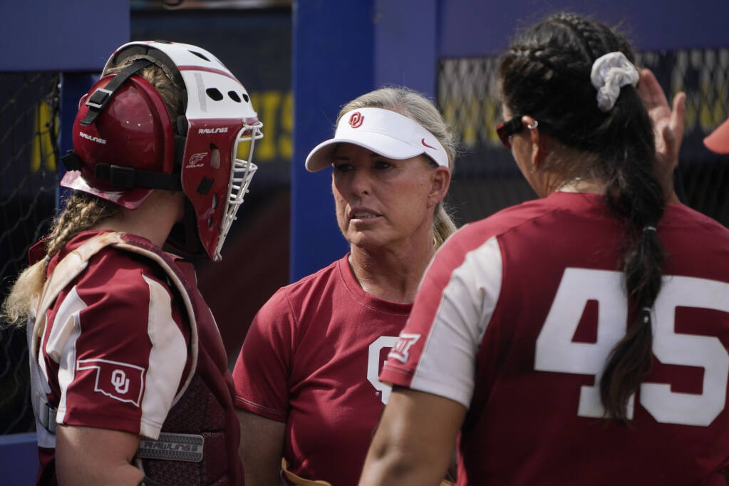 Oklahoma coach Patty Gasso, center, talks with catcher Lynnsie Elam, left and pitcher Giselle Juarez during the team's Women's College World Series softball game against James Madison on Monday, June 7, 2021, in Oklahoma City. (Sue Ogrocki / ASSOCIATED PRESS)