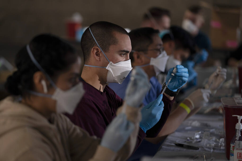 Members of the National Guard fill syringes with Pfizer's COVID-19 vaccine at a vaccination site in Long Beach, Calif., Friday, March 5, 2021.  (AP Photo/Jae C. Hong)