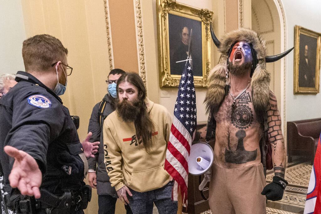 Rioters confront a police officer in the Capitol after then-President Donald Trump told them election results could be reversed. Clarifying the law could prevent a repeat of the Jan. 6 riot. (MANUEL BALCE CENETA / Associated Press)