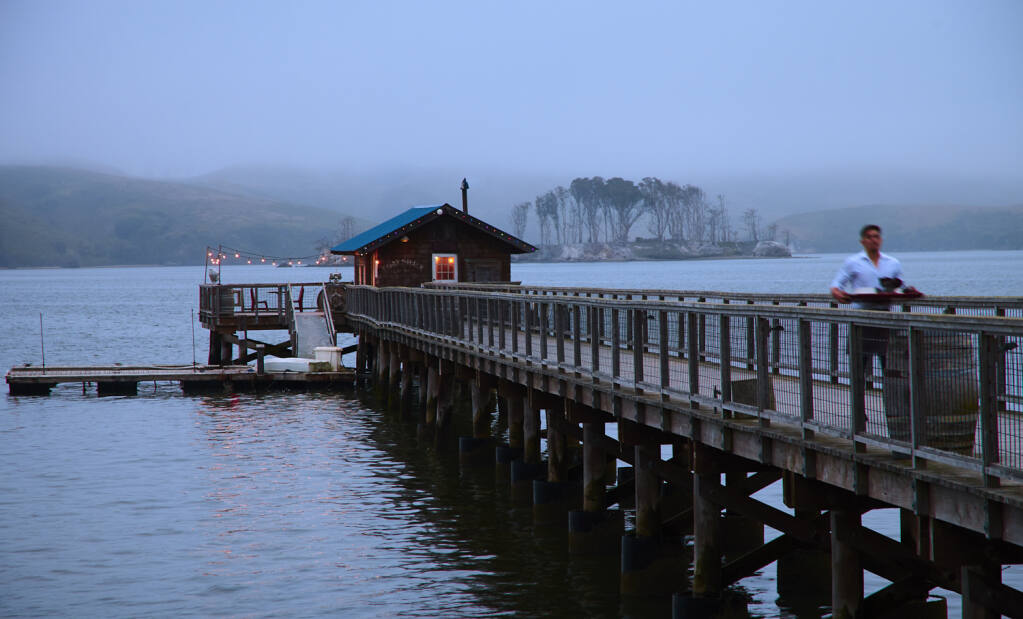 Nick's Cove Restaurant & Cottages features a 400-foot-long pier with a rustic fishing shack at the end that serves as a private dining room. Hog Island is in the background. (Frankie Frankeny/Cameron + Company)