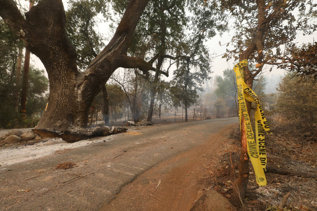 Crime scene tape marks an area along North Fork Crystal Springs Road where investigators have been looking into the cause of the Glass fire near Deer Park on Thursday, Oct. 1, 2020.  (Christopher Chung/ The Press Democrat)