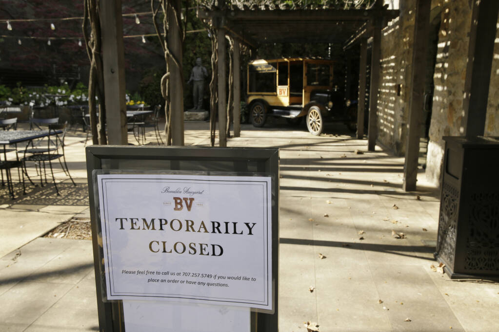 In this photo taken Thursday, March 19, 2020, a temporarily closed sign is posted outside the entrance to the Georges De Latour Reserve Tasting Room at the Beaulieu Vineyard winery in Rutherfod. The tasting room reopened June 20 under new Napa County safety guidelines. (AP Photo/Eric Risberg)
