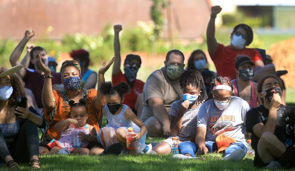 During the Uplifting Black Leaders social justice protest at Santa Rosa Junior College, people take cover in the shade and react as organizers speak to the crowd prior to a march to Old Courthouse Square in Santa Rosa, Saturday, July 11, 2020.   (Kent Porter / The Press Democrat) 2020