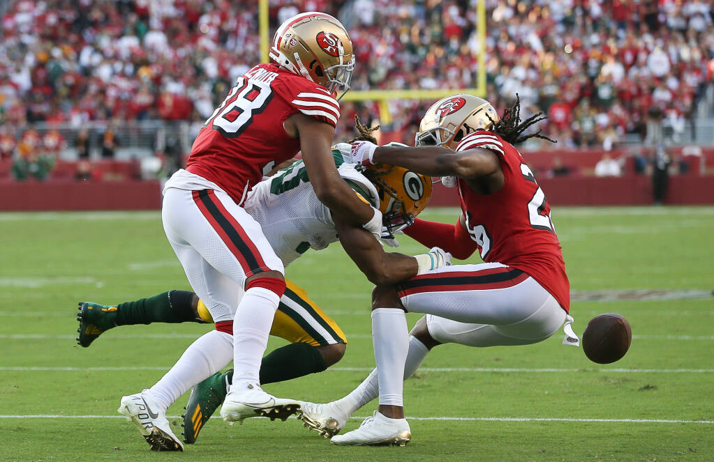 San Francisco 49ers defenders Deommodore Lenoir, left, and Josh Norman hit Green Bay Packers' Aaron Jones to force the ball loose during their game in Santa Clara on Sunday, September 26, 2021.  (Christopher Chung/ The Press Democrat)