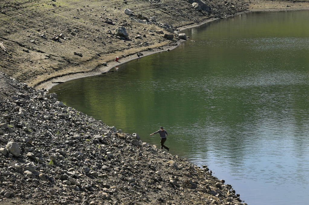 A fisherman tries his luck along the receding shoreline at Lake Sonoma, where the impacts of a dry winter are increasingly apparent. (KENT PORTER / The Press Democrat)