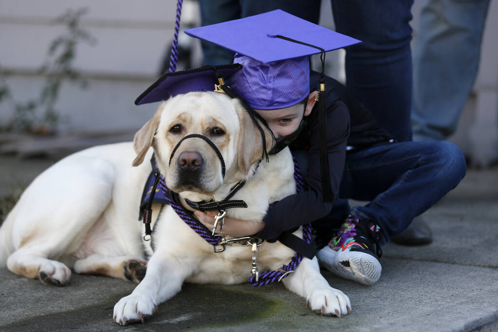 Max Stiles, 5, hugs his service dog Casper after a surprise graduation ceremony from the Paws As Loving Support (PALS) Assistance Dogs program outside his home in Santa Rosa, California, on Sunday, Jan. 17, 2021. (Beth Schlanker / The Press Democrat)