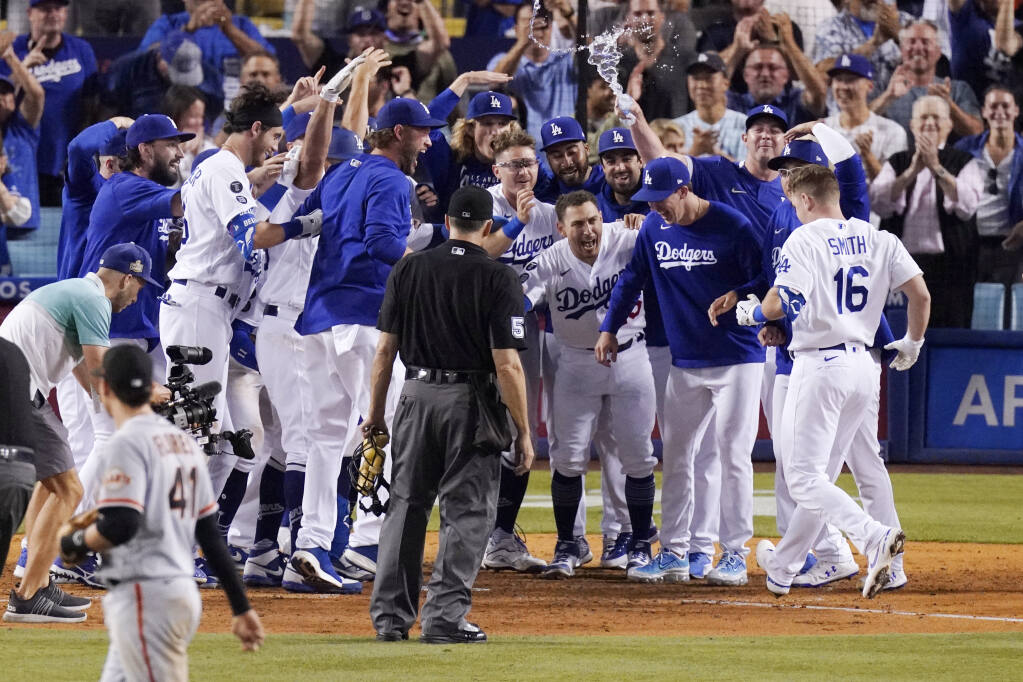 Members of the Los Angeles Dodgers celebrate as Will Smith, right, scores after hitting a three-run walk off home run during the ninth inning against the San Francisco Giants on Tuesday, July 20, 2021, in Los Angeles. (Mark J. Terrill / ASSOCIATED PRESS)