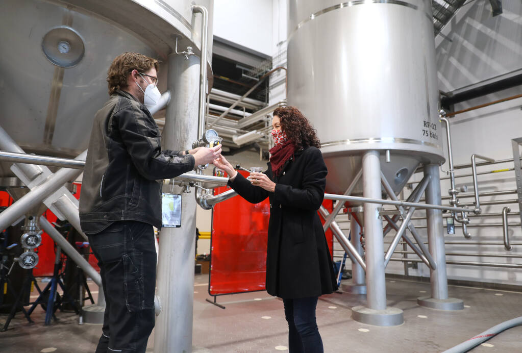 Russian River Brewing Co. production manager Stephen Rawlings, left, and co-owner Natalie Cilurzo taste a sample of Pliny the Younger from a tank at the brewery in Windsor on Tuesday, Jan. 26, 2021. (Christopher Chung / The Press Democrat)