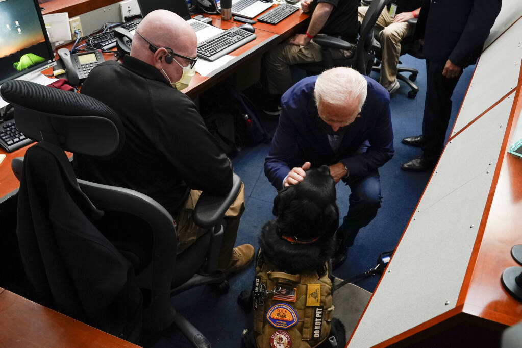 President Joe Biden pets a service dog during a briefing on wildfires at the California Governor's Office of Emergency Services, Monday, Sept. 13, 2021, in Mather, Calif. (AP Photo/Evan Vucci)