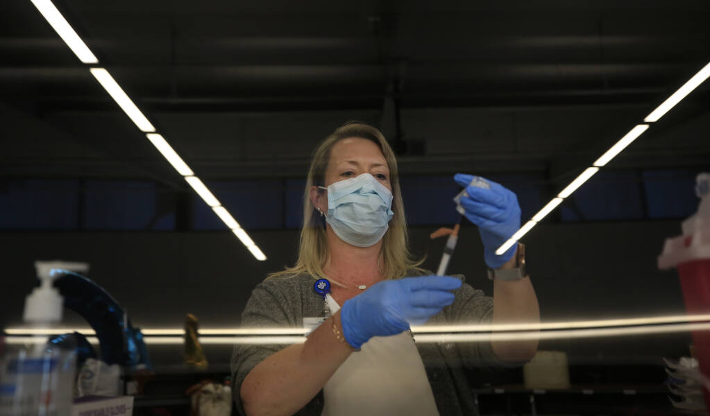 Brandi Lazorek draws vaccine from behind plexiglass at a COVID vaccination clinic in Napa, Wednesday, March 31, 2021.  Lazorek has spent the pandemic commuting between Humboldt, Sonoma and Mendocino counties with Providence Medical Group making sure nurses under her command are up to date on proper procedures and have enough PPE.  (Kent Porter / The Press Democrat) 2021